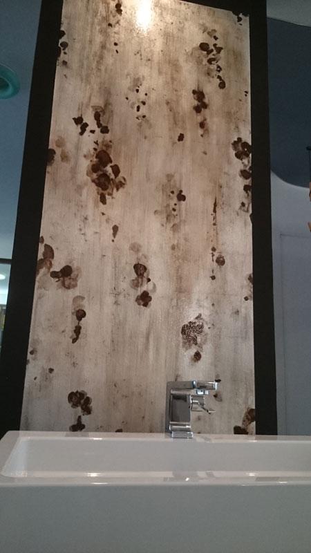 Aluminium Wand mit Waschbecken davor.