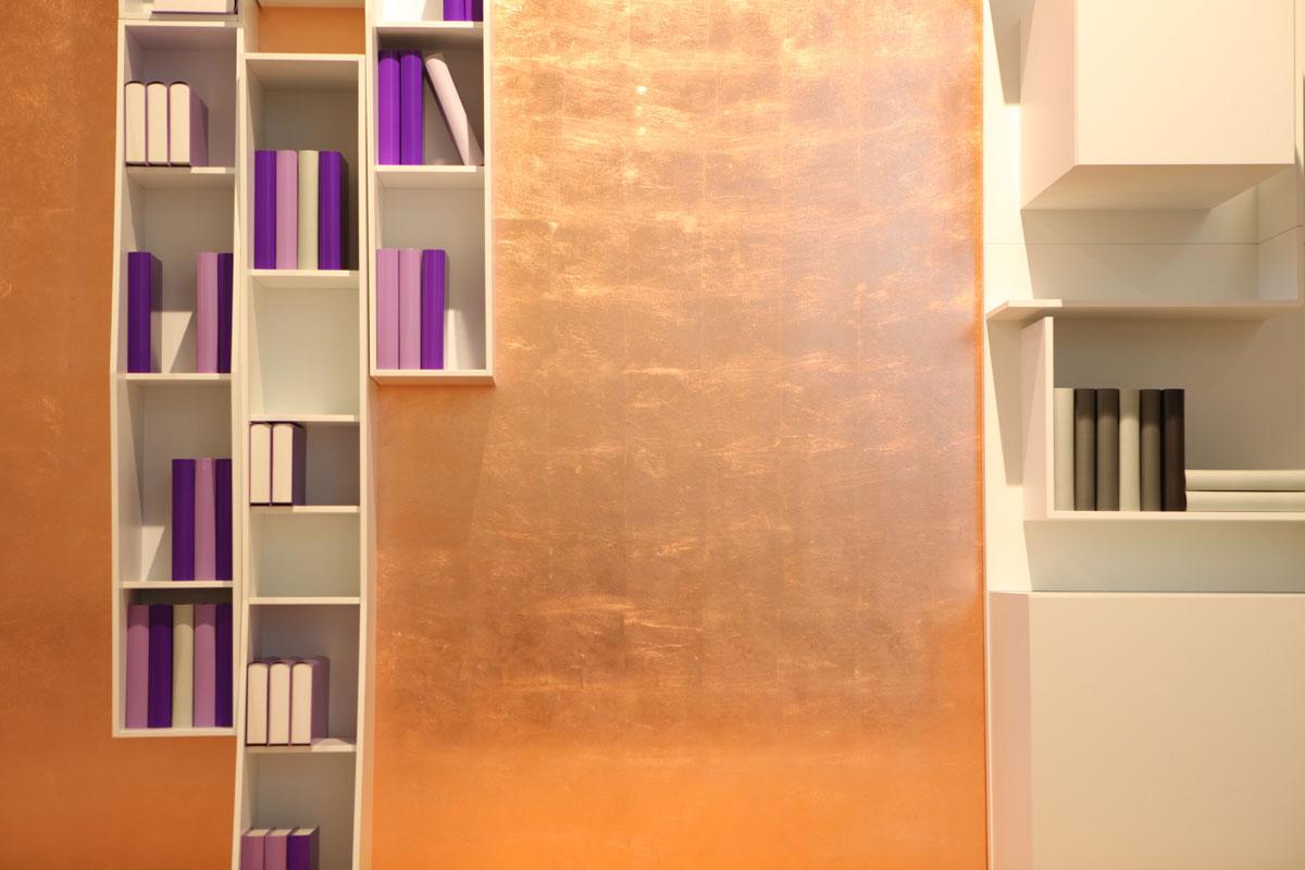 Kupfergestaltung hinter Wandregalen.
